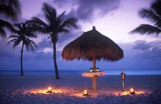 Romantic palapa on beach at dusk, Aruba, Caribbean (© Ocean/Corbis)