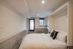 white painted brick wall with cream/light greige trim and black doors and windows, all with can lights to brighten the space