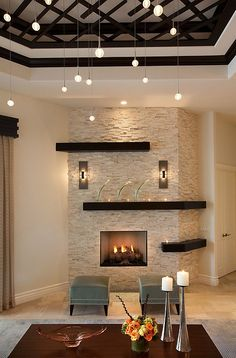 The focal stone wall with mantels are great! love the contrast of light stone and dark wood as well as the ceiling treatment!