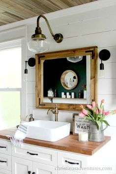 Farmhouse bathroom vanity - white cabinets, black hardware, butcher block countertops, aged brass. Every detail of this bathroom is stunning!