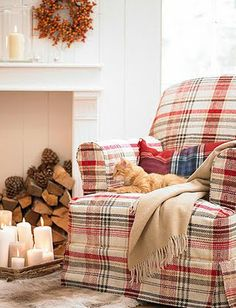 chair, blanket on chair, stacked wood, colors, candles on low table, on fireplace/wood