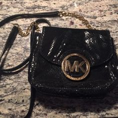 Black snakeskin Michael Kors crossbody It's a black Snake skin (fake) crossbody by Michael Kors. I've used it a lot but just got a new black crossbody so I don't have a need for this. the metal is scratched but overall it's a great crossbody for going out Michael Kors Bags Crossbody Bags