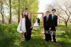 Groom and bride's children hold a frame around the kissing couple. Blended family. Cherry blossoms. Door County wedding sneak peek by Jason Mann Photography 920-246-8106 www,JMannPhoto.com