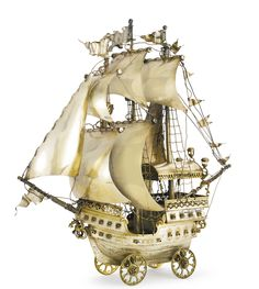 A German silver-gilt nef, Hanau, retailed by Buchholz & Zelt, New York, circa 1900 the three-masted ship fully rigged with seven sails, flying pennants, cannons, and sailors on duty, with a dragon and shield figure-head, on four wheels marked on hull height 16 1/8 in.