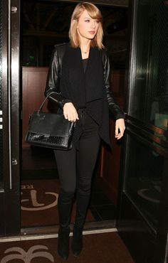 Taylor Swift wears a black scarf, moto jacket, skinny jeans, top-handle bag, and black booties
