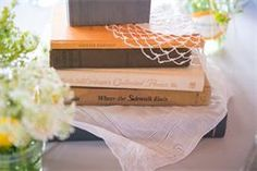 Book/novel themed wedding reception. Each novel was hand chosen by the bride for each table, and specific to the Bride and Groom. Seating cards were library book checkout slips. They were held in place by multiple folded pages of books.