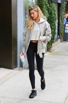 Hailey Baldwin in casual in a Fear of God jacket, cropped hoodie, Alo Yoga leggings, and Nike shoes