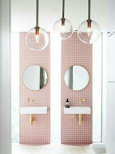 Idée de salle de bain pour enfant : des bandes verticales de faïence roses, robinetterie dorée, miroirs ronds et abat jour en verre