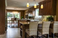Natural fiber barstools add warmth and texture to the design of this traditional kitchen. Mother of pearl pendant lights tie in with the mother of pearl chandelier in the dining area, contributing another natural element.