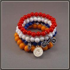 Handgemaakte elastische armband van acryl basiskralen. Rood/wit/blauw 8mm ronde kraal en oranje 10mm ronde kraal. Met 3 zilverkleurige bedels in HOLLAND thema: de oude vertrouwde omafiets, een tulp en de ode aan de gulden, het dubbeltje
