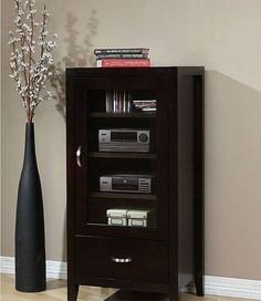 Store and protect your stereo in this Axium espresso audio cabinet. Three adjustable shelves behind an elegant glass door offer room for your audio components and media collection, and a lower drawer provides ample storage for cords and peripherals.