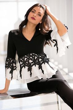3603adfa2c6d Cascading black lace creates colorblock detail on the tiered ruffle hem and  bell sleeves of our