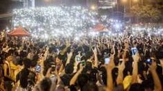 Pro-democracy protesters hold up their mobile phones as lights in front of the Hong Kong government offices on day three of the mass civil disobedience campaign Occupy Central in Hong Kong: Who is biased? The West or China?
