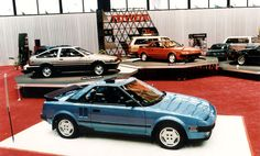 1985 Chicago Auto Show. A two-passenger MR2 sport coupe dominates the foreground of this scene at Toyota's main-floor exhibit space. Evolved from an SV-3 prototype, the MR2 arrived at U.S. dealerships in February 1985--right at the time of the Chicago Auto Show. Angular styling gave the MR2 a different look than conventional sports cars. Additional Toyotas may be seen toward the rear, including a Corolla Liftback coupe at left, on a raised platform, and another MR2 on the center platform.