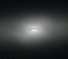 NGC 4526 : Lenticular Galaxy - Located about 55 million light-years away in the Virgo Cluster, this galaxy has a supermassive blackhole that is around 450 million times the mass of our Sun. The disk of dust has a spin rate of about 155.34 mps / 250 km/per sec. Ground-based observations have shown about a quarter of the lenticular galaxies in the cluster seem to have rapidly rotating disks in their centers - NASA/ESA/Hubble - acknowledgement : Judy Schmidt