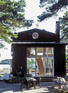 Black house with white roof (energy-saving) and white window frames. And huge windows.
