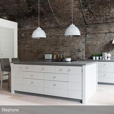 In hohen Räumen setzen große Leuchten auffällige Akzente: Pendelleuchten in Weiß beispielsweise setzen sich von der rauen Backsteinwand und Decke ab und…