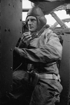 The flight engineer of a Handley-Page Halifax of No. 35 Squadron RAF, at his work station aft of the pilot's position, prior to take-off from Linton-on-Ouse, Yorkshire. He is wearing a Type B helmet and 1930 Pattern flying suit.