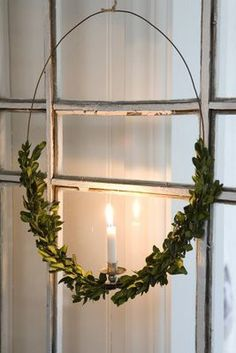 Wunderschöne Fensterdeko zu Weihnachten. Kranz aus Metall mit Buchsbaum und kleiner Kerze.