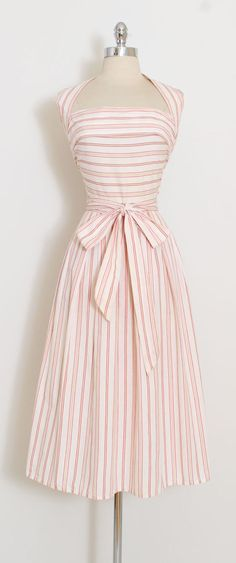 ➳ vintage 1940s dress * convertible halter dress by iconic American designer, Claire McCardell * white ticking stripe cotton in red and golden yellow * tie halter straps that wrap and close at front or back * right hip pocket * metal side zipper * noteworthy and rare piece of fashion history condition | excellent - only flaw to note is inconspicuous needle marks at back center of bodice where it was taken in and let out. fits like xs/s length 48 bodice length 18 bust 36 waist 26-27 ➳...