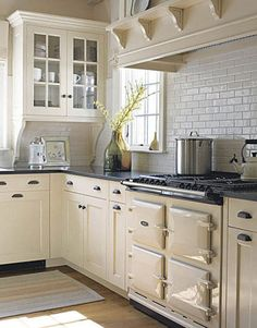 Cream and white color kitchen; stove; cabinetry | Interior Designer: Susan Tully