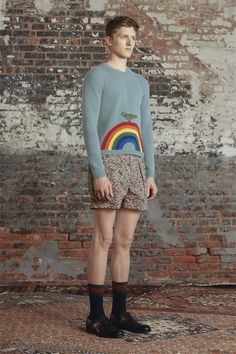 Gucci Look 37 from the Men's Cruise 2016 Collection features a light blue wool sweater with bird and rainbow details paired with loose-fitting silk twill short with Gucci's heraldic print.