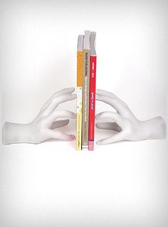 Turn your bookshelves into a mini art gallery with these sculptural hand shaped bookends. The weighted realistic looking white plastic hands look delicate but prop up your book collections with ease. Slightly distressed finish, may have lightly darkened areas (usually near the wrist on each hand).