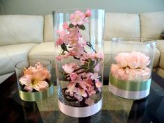 Cylindrical Vases filled with Cherry blossoms, roses and lilies. All in shades of pink. Choice of Florals and colors. Call or email for pricing info. savannahdecor@yahoo.comvendors: Savannah Event Decor