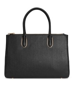 Handbag in thick, grained imitation leather with metal details. Three compartments, two with zip. Two handles and detachable shoulder strap at top, snap fasteners at sides to adjust volume of bag, three inner pockets, one with zip, and studs at base. Lined. Size 6 1/4 x 10 1/2 x 14 1/2 in.