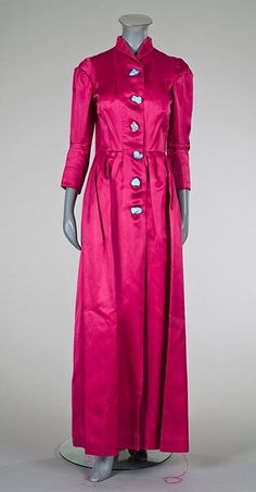 Schiaparelli couture shocking pink coat-dress, late 1930s-early 1940s, printed red on white Schiaparelli Paris label, numbered 50928, fastening by five detachable chunky turquoise buttons, the lower hem internally fastened with loops and six self-covered small buttons.