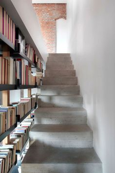 9 Stylish Staircases With Bookshelves As Safety Barriers // These concrete stairs are brightened up by the light shining through the open bookshelf.