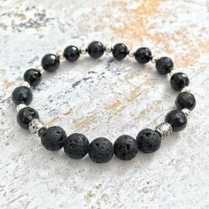 ESSENTIAL OIL DIFFUSER BRACELET This gemstone stretch bracelet is made with Malaysian Jade beads dyed black and Lava Stone beads for diffusing essential oils. Accented with silver metal beads, this basic black bracelet is functional and great for everyday wear! Pretty enough to wear