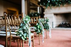 loose and organic pew markers of seeded eucalyptus and lemon leaf are simply tied with ivory satin ribbon onto gold chiavari chairs.