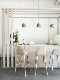 Houten barkrukken en groene hanglampen in keuken