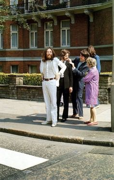 Just before the famous Abbey Road photo was taken, The Beatles were photographed on the sidewalk waiting to cross the street.