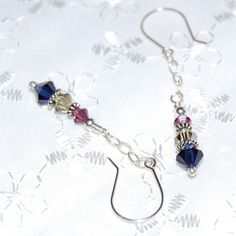 Swarovski crystals in Indigo Blue, Jonquil Satin, and Amethyst dangle from sparkly sterling silver open link chain with Bali silver spacers. The sterling ear wires and fine silver headpins are also handmade by me. Measures approximately 2 inches in length. I have many colors to choose from. If you would prefer another color scheme, please note your preference, and I will gladly customize this design to suit your needs.