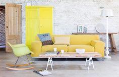 White washed bricks wall and yellow pale sofa