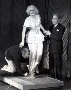 Jean Harlow putting her footprints in cement at Grauman's Chinese Theatre. (1933)