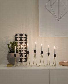 Adventsstake fra Konstsmide i messing og sorte detaljer med 7 hvite stavlamper. Staken har en retro og vakker design med en buet metallstang i messing som starter og slutter i en koblingsboks.