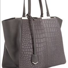 3jours Fendi Satchel Brand New Grey Fur 3 Jours is a timeless design to endure season after season, this impeccably crafted and highly coveted style features winged sides that form an architectural silhouette, its body rendered in an exquisite mix of crocodile-embossed calf hair and rich leather.  Signature metal and lacquer logo bars at top line; polished silvertone hardware; protective metal feet at base Lined with suede; one zip pocket and two slip pockets at interior Snap-button tab…