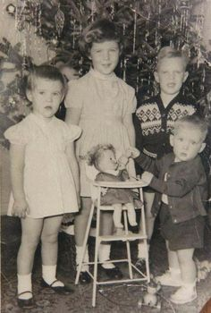 Children in front of the tree on Christmas morning ~ looks like someone got a doll!