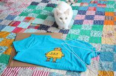 Här är allt du behöver: T-shirt (storlek beror på hur stort eller litet tält du vill ha), två stålgalgar, en bit kartong, tjockare tejp, säkerhetsnålar och tång.