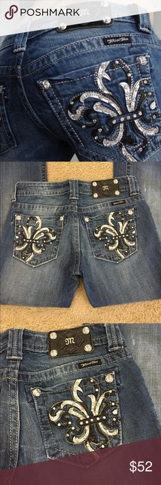 """🌿Miss Me #JP6073B elegant fleur de lis jean sz 26 🌿Miss Me #JP6073B elegant fleur de lis medium wash boot cut jeans sz 26. These are some of my favorite jeans! The back pocket has silver and black leather design for a stunning look! Very on trend. Preloved in excellent condition. All rivets and Rhinestones intact. Small place on front right leg-pictured. Slight discoloration. Priced accordingly. Waist lying flat is 14.5"""". Rise 7"""". Inseam 34"""". Outseam 41"""". Boot 8.5"""". Miss Me Jeans Boot Cut"""