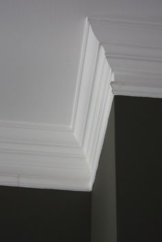 Trick to faking thick crown molding.   First, install a basic crown molding.  Then, about 3 inches below the crown, install a decorative picture frame molding.  Caulk the seams. Then paint the two trims and space in between with same color. Appears to be one large thick piece... Love!