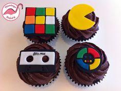 80s themed cupcakes.   Rubik's cube, Pac-Man, mix tape & Simon (remember that?)    www.flamingobakery.co.uk