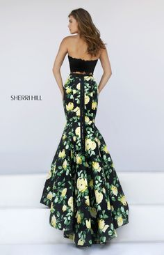 The Sherri Hill 50026 is a youthful two-piece prom dress, designed with a lace crop top and a floral print skirt. Beaded lace coats the halter top, leaving a frilled trim all over. A slim waistband caps the mermaid skirt, and ties into a dainty bow above the gorgeous court train.