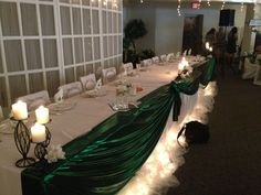 Head table had metallic green fabric draped in front with black iron candleholders and the wedding party's paper flower bouquets