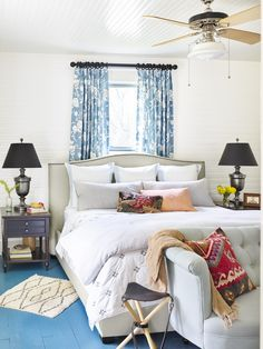 To make the best use of the bedroom space, the bed was places in front of a window with bold draperies. Lamps flank the bed and a tufted linen settee complete the focal point.