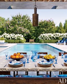 Outdoor dining room overlooking the pool in a home in Southampton, NY designed by by Juan Montoya Design