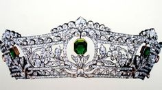The Harcourt Tiara, by Boucheron.  Antique emerald and diamond tiara. Comprising seven graduated step-cut emeralds set within sprays of diamond flowerheads and leaves, running between borders of continuous diamond collets and ribbon motifs, mounted in silver and gold, circa 1900, 43.8 cm. inner circumference.